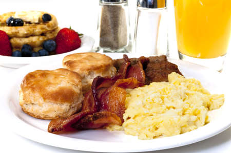 Big country breakfast with scrambled eggs, bacon, buttermilk biscuits, waffles, fruit, and orange juice.