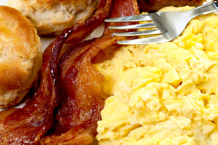 scrambled: Closeup of scrambled eggs, bacon slices, biscuits, and fork
