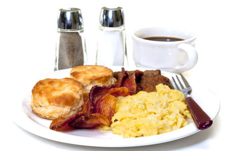 biscuits: Big country breakfast with scrambled eggs, bacon, sausage, buttermilk biscuits, and coffee.  Salt and pepper shakers in background.  Isolated on white background.