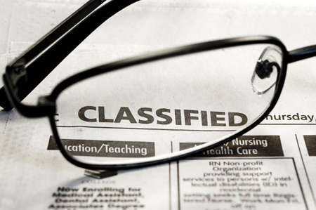 Closeup of classified ads in newspaper with reading glasses. Фото со стока