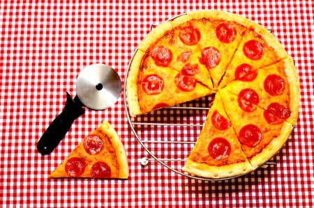 Whole pepperoni pizza with slice removed and cutter.  Pizza is on rack with cutter on table.  Items are on red gingham tablecloth.