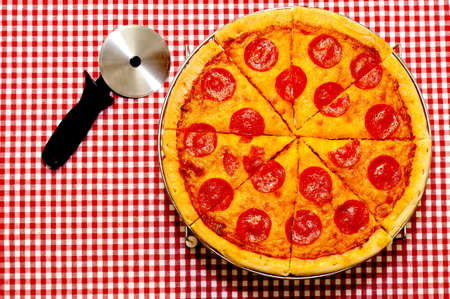 pastry cutter: Sliced whole pepperoni pizza with cutter on red gingham tablecloth.
