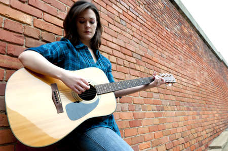Young woman playing guitar outside while leaning against brick wall.