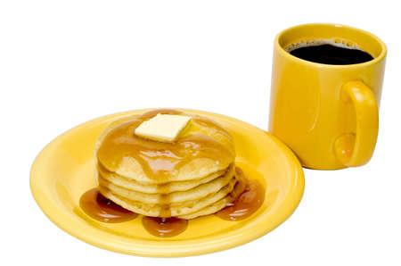 バック グラウンドでのコーヒー サービスとの板にバターとメープル シロップのパンケーキのスタック。クリッピング パスと白色の背景上に分離。