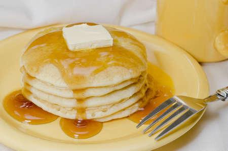panqueques: Pila de panqueques con mantequilla, jarabe de arce, y un tenedor. Café en el fondo.