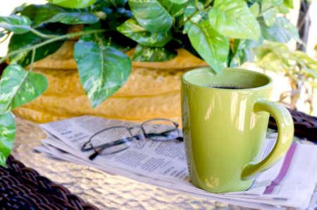 Morning coffee with newspaper and reading glasses   Green plant in background