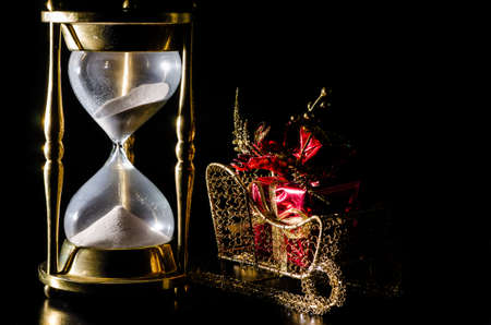 Christmas gift on sleigh and hourglass on black background   Concept showing time running out for Christmas shopping  photo