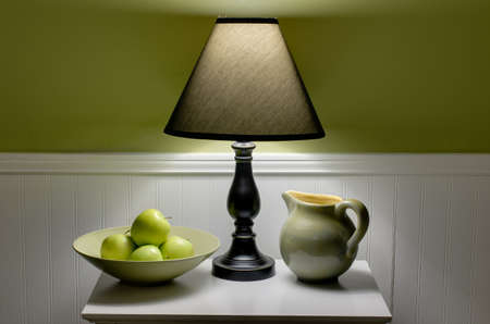 Bowl of green apples, lamp and pitcher on table.  Scene is illuminated only by soft light from lamp. 写真素材