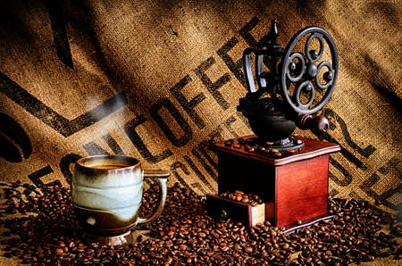 jamoke: Cup of steaming hot coffee with coffee beans, coffee grinder, and coffee beans bag in background. Stock Photo