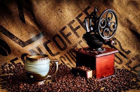 semilla de cafe: Taza de humeante caf� caliente con granos de caf�, molinillo de caf� y caf� frijol bolsa en el fondo.