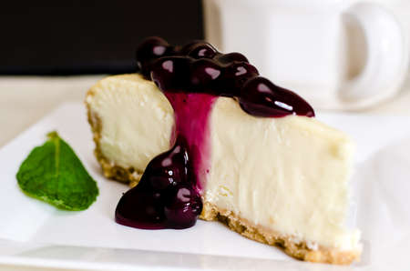 Slice of blueberry cheesecake and coffee with mint garnish.  Shallow depth of field. photo