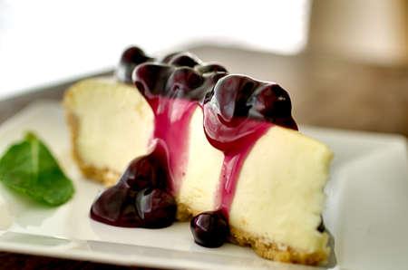 Segment van blueberry cheesecake in de middag met munt garnering. Ondiepe scherptediepte.