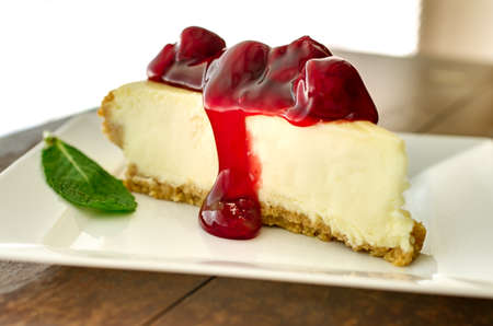 Slice of cherry cheesecake in the afternoon with mint garnish.   Shallow depth of field.