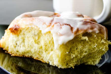 Closeup of cinnamon bun and coffee.