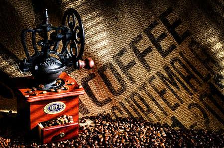 młynek do kawy: Puchar parze gorącej kawy z ziaren kawy, młynek do kawy i ziaren kawy worek w tle.