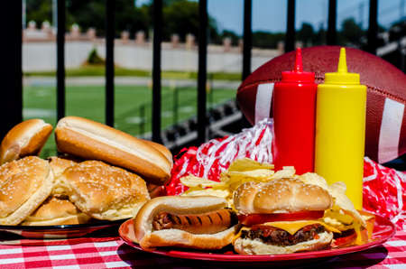 Football party with cheeseburger, hot dog, potato chips, pom poms, buns, and football   Football field in background  Stock Photo