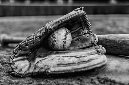 days gone by: Baseball glory days with ball in glove and bat on base on field   Monochrome image with outfield wall in background