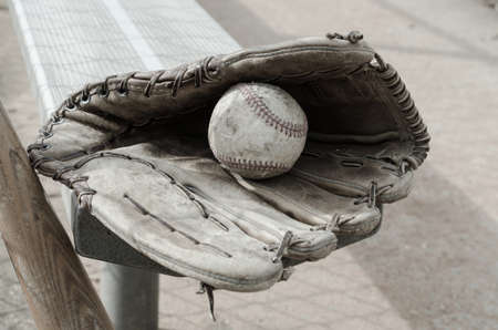 dugout: Baseball times gone by with ball and glove on bench in dugout with bat
