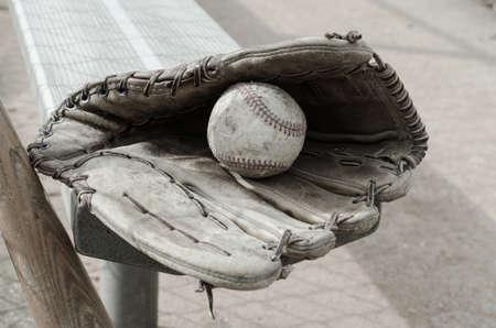 baseball dugout: Veces B�isbol pasados ??con la bola y el guante en el banco en el dugout con el bate