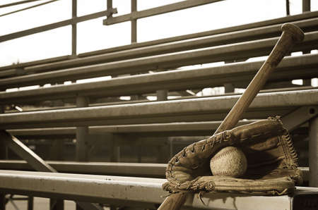 High school baseball practice with ball in glove and bat on bleachers    Stock Photo