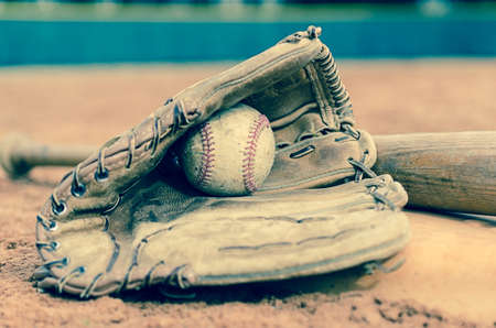 Traditional baseball with ball in glove and bat on base on field   Outfield wall in background  Stock Photo - 25971150