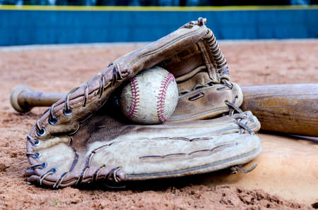 Baseball bat, glove, and ball on base on field    Stock Photo - 25970915