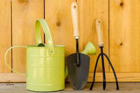 Gardening tools with watering can, trowel, and hand cultivator on wood background  写真素材