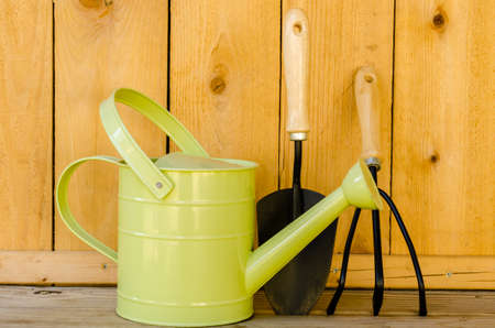 Garden tools with watering can, trowel, and hand cultivator on wood background  写真素材