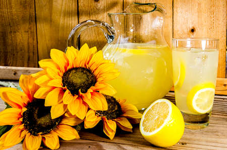 Summer lemonade with lemon slices, pitcher, and sunflowers on wood bench.   写真素材