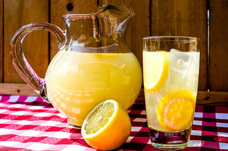 Lemonade and pitcher with sliced lemons on red gingham table cloth.  photo