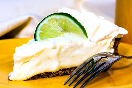 Key lime pie closeup with fork on plate.