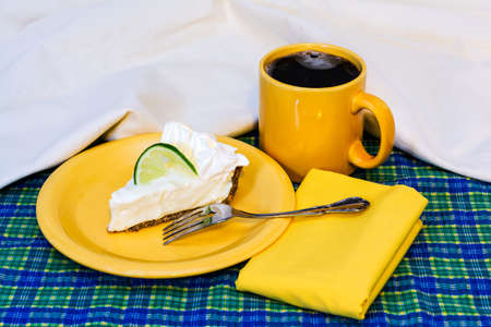 Slice of key lime pie with coffee on plate with fork and napkin.