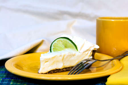 Slice of key lime pie with coffee closeup on plate with fork and napkin.