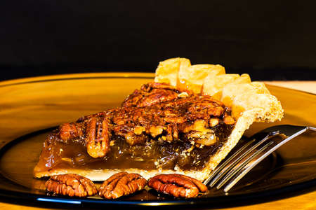 Pecan pie closeup with fork on plate.