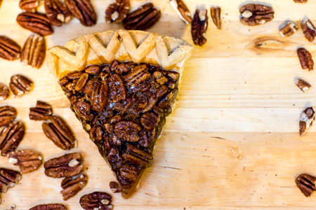 Pecan pie slice and pecans with copy space.
