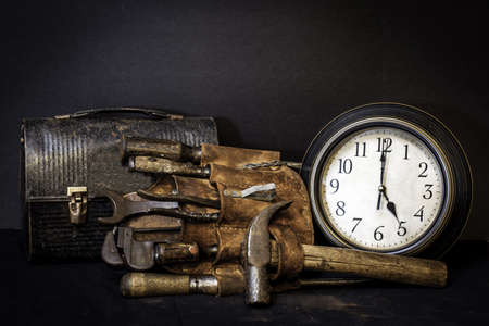 quitting: Quittin time.  Vintage tool belt and lunch box with tools and clock showing 5 o