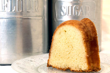 Slice of pound cake closeup with flour and sugar canisters in background.