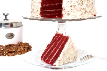 whole pecans: Slice of red velvet cake removed from whole cake which is in background along with sliced pecans and sugar canister.  Slice of cake is on plate along with fork.  Isolated on white background. Stock Photo