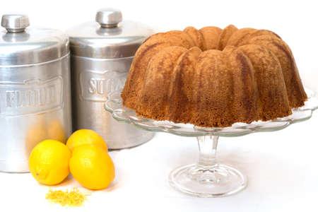 Lemon pound cake with lemons, lemon zest, flour and sugar canisters.
