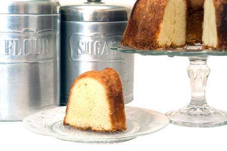 Slice of pound cake removed from whole cake which is in background along with flour and sugar canisters.  Isolated on white background with clipping path. 写真素材