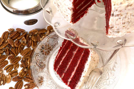 Slice of red velvet cake and pecans with sugar canister in background.  Slice is removed from whole cake which is in background.  Fork is on plate.