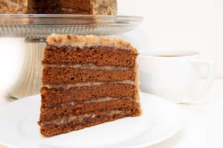 German chocolate cake slice closeup with coffee.  Slice is removed from whole cake which is in background.