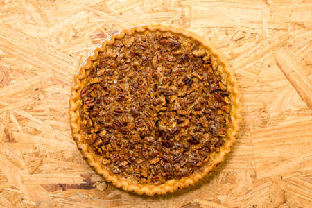Whole pecan pie on wooden background.  Overhead view.