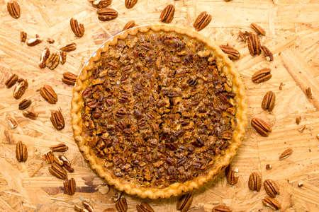 Pecan pie with pecans on wooden background.  Overhead view.