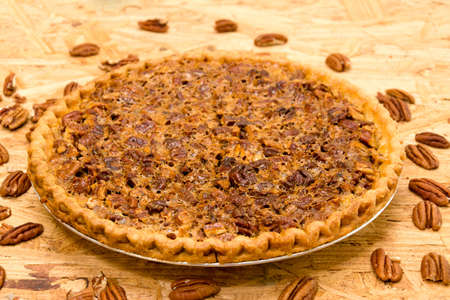pastry crust: Whole pecan pie with pecans on wooden background. Stock Photo