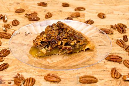 Pecan pie slice with pecans on wooden background
