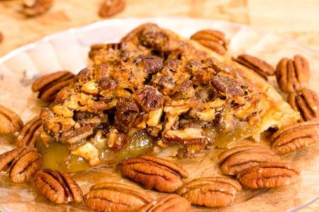 Pecan pie slice closeup with pecans on wooden background.