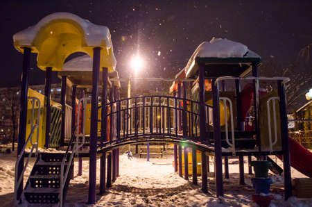 Snow-covered playground at night in the city in winter.
