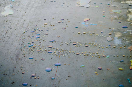 Rainbow chemical stains on the water in a puddle on road