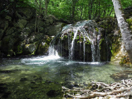 Beautiful waterfall with natural pool in the mountin forest. Cascading river on Crimean mountains at spring Stock Photo